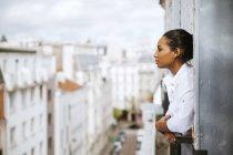França, Paris, jovem mulher no sótão inclinada para fora da janela — Fotografia de Stock