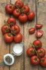 Tomates de Viña y vaso de sal marina - foto de stock