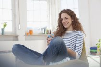 Smiling woman at home sitting in chair — Stock Photo