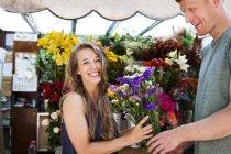 L'homme dons fleurs pour copine souriante — Photo de stock