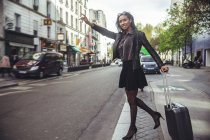 France, Paris, young woman hailing a taxi — Stock Photo