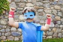 Маленький большой герой в маске у каменной стены — стоковое фото