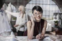 Concepteur de robe de mariée parlant au téléphone dans le magasin de mariée — Photo de stock
