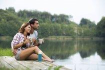 Розслабленої молода пара з гуртки кави, сидячи на пристані на озері, дивлячись на відстань — стокове фото