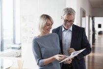 Бизнесмен и бизнесвумен, обсуждая документы в офисе — стоковое фото