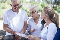 Casal de idosos com ar livre de instrutor de fitness — Fotografia de Stock