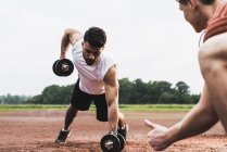 Athlete exercising with dumbbells on sports field supported by his training partner — Stock Photo