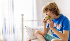 Portrait of boy sitting on the couch eating an apple — Stock Photo