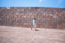 Ragazzo camminando davanti al muro di mattoni — Foto stock