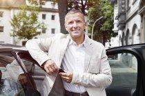 Retrato de hombre sonriente apoyado en la puerta de coche abierto con las llaves del coche - foto de stock