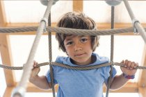 Portrait of little boy on hanging bridge of a playground — Stock Photo