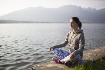 Italy, Lecco, relaxed young woman sitting at the lakeshore — Stock Photo