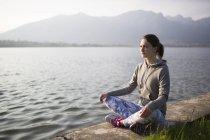 Italie, Lecco, détendue jeune femme assise au bord du lac — Photo de stock