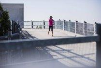 Молодая женщина бежит по парковке — стоковое фото