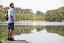 Молода людина стоїть на пристані на озері, дивлячись на відстань — стокове фото