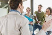 Trois collègues heureux au bureau regardant parler femme mûre — Photo de stock