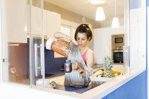 Junge Frau in Küche schüttet Smoothie in Becher — Stockfoto