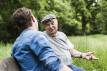 Portrait of senior man sitting on a bench talking to his grandson — Stock Photo