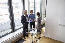 Drei Unternehmerinnen sprechen am Fenster im modernen Büro — Stockfoto