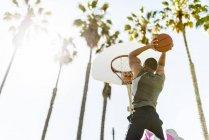 Jeune homme jouant au basketball sur cour extérieure — Photo de stock