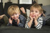Deux petits garçons jouant à la maison, allongés sur le canapé — Photo de stock