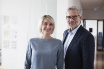 Kaufmann und Kauffrau im Büro stehen und Blick in die Kamera — Stockfoto