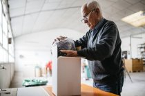 Senior Man das fertige keramische Stück Verpackung — Stockfoto