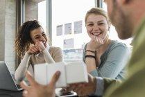 Tres colegas sonrientes en la oficina trabajando juntos - foto de stock