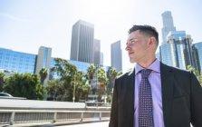Бизнесмен оглядывается вокруг, город на заднем плане — стоковое фото