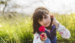 Portrait of little girl with red flower in nature — Stock Photo