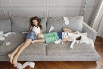 Frères et sœurs couchés sur le canapé entourés par le désordre des morceaux de papier toilette — Photo de stock