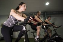 People training on exercise bikes in gym — Stock Photo