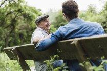 Riant senior homme assis sur un banc avec son petit-fils — Photo de stock