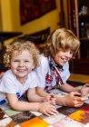 Deux garçons, allongé sur le sol à la maison en jouant avec tablette numérique — Photo de stock