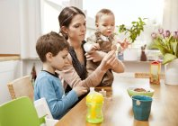 Mother with her little sons in the kitchen — Stock Photo