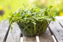 Rucola fresca in cestino sulla tavola di legno — Foto stock