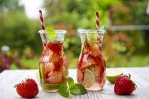 Duas garrafas de vidro de água de desintoxicação infundida com morangos e limão — Fotografia de Stock