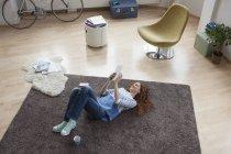 Mujer en casa acostada en el suelo usando tableta digital — Stock Photo