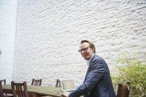 Бизнесмен сидит с ноутбуком за столом на заднем дворе и смотрит в камеру — стоковое фото