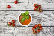 Tomato soup and tomatoes on wood — Stock Photo