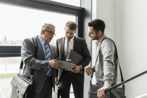 Three businessmen with digital tablet talking in staircase — Stock Photo