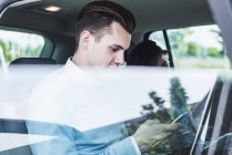 Young man with cell phone and woman in car — Stock Photo