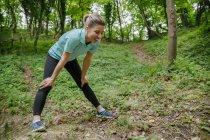 Усміхаючись спортсменка, відпочиваючи в лісі — стокове фото