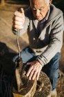 Hombre superior usando una herramienta antigua para agrietar las nueces - foto de stock