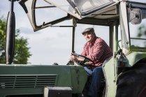 Agriculteur assis dans le tracteur — Photo de stock