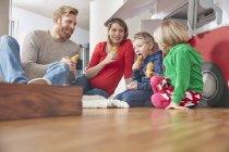 Счастливая семья ест мороженое в гостиной — стоковое фото