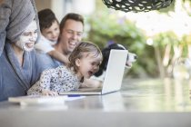 Family sitting on terrace looking together at laptop — Stock Photo