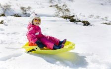 Happy girl with sledge in the snow — Stock Photo