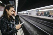 Улыбаясь молодая женщина на вокзал, глядя на сотовый телефон — стоковое фото