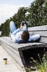 Young man lying on bench using smart phone — Stock Photo